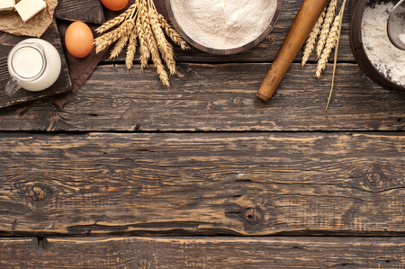 Photo for flour in a wooden bowl on dark wooden background with spikelets of wheat, eggs, milk and butter, top view with copy space. ingredients for bakery products - Royalty Free Image