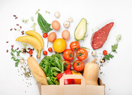 Photo pour Full paper bag of different health food on a white background. Top view. Flat lay - image libre de droit
