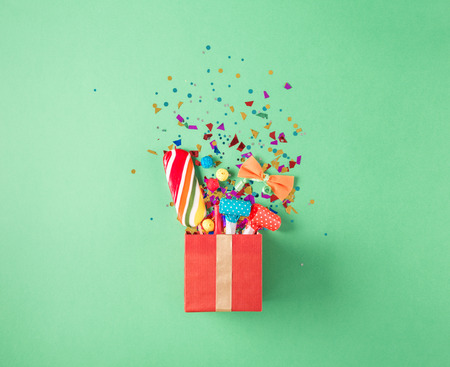 Photo for Red gift box with various party confetti, balloons, streamers, noisemakers and decoration on a green background. Flat lay - Royalty Free Image