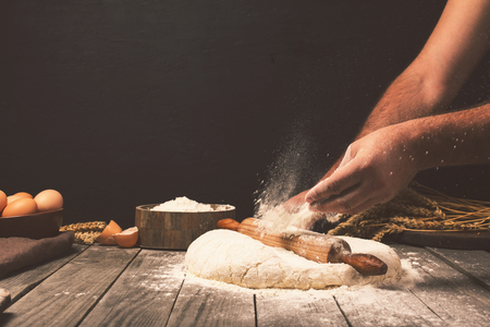 Foto de Men hands sprinkle a dough with flour close up. Man preparing bread dough - Imagen libre de derechos
