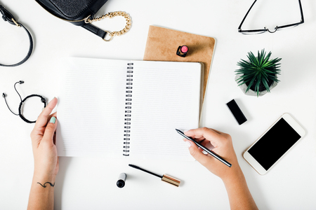 Foto de Woman hands writing in a notebook on a white table with female accessories. Concept feminine working place - Imagen libre de derechos