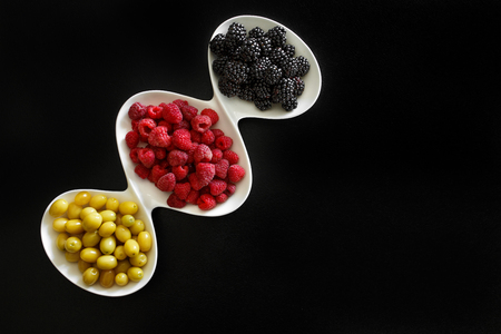Photo for juicy raspberry, blackberries and dogeberry in white plate on black background - Royalty Free Image
