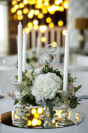 Wedding table setting is decorated with fresh flowers and white candles. Wedding floristry. Bouquet with roses, hydrangea and eustoma. On the background blur are burning garlands with light bulbs.