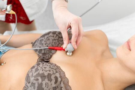 Foto de Doctor attaches ECG sensors to the patient chest. - Imagen libre de derechos