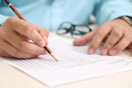 Photo for Man is filling OMR sheet with pencil. - Royalty Free Image