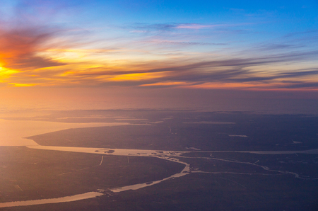 Photo pour beautiful sunset with aerial view of sea and river from airplane, plane, window seat over Netherlands, Europe - image libre de droit