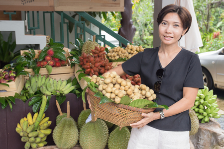 Photo for Asian woman with tropical fruit basket in the market - Royalty Free Image