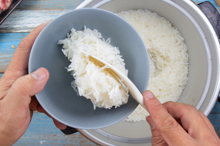 Photo for Chef put cooked rice with plastic ladle to cup in electric rice cooker - Royalty Free Image