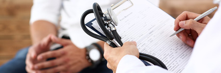 Foto de Male doctor hand hold silver pen filling patient history list at clipboard pad. Physical, exam, er, disease prevention, ward round, visit check, 911, prescribe remedy, healthy lifestyle concept - Imagen libre de derechos