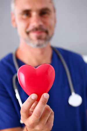 Foto de Male doctor wearing blue uniform hold in arms red toy heart closeup. Cardio therapeutist, student education, CPR, 911 life save, physician make cardiac physical, pulse rate measure, arrhythmia - Imagen libre de derechos