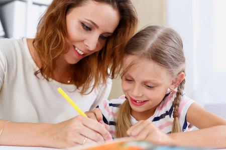 Foto de Blond smiling little girl hold in arm pencil drawing something together with mom. Beautiful female young artist, minor baby-sitter, art joy, juvenile development, parent lifestyle, youth, painter - Imagen libre de derechos