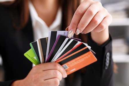 Photo pour Female arm hold bunch of credit cards picking one closeup. Convenient set of funds, budget wallet deposit, wealth and effective investment, invest resources, income profit concept - image libre de droit