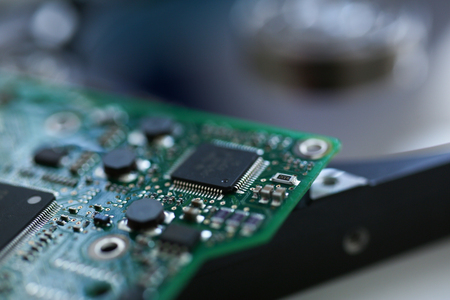 Foto de Electronic board with microchips on a hard drive background in a repair workshop background - Imagen libre de derechos
