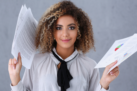 Photo pour Beautiful black woman portrait. Holds paper documents with financial statistics fashion style mulatto curly hair with white locks eye view of the camera lot of work - image libre de droit