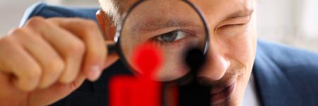 Photo pour Man in suit look thru loupe on statuettes closeup - image libre de droit