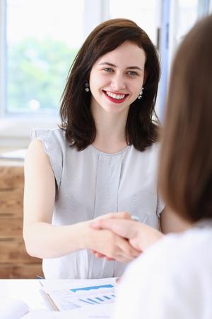 Photo pour Business woman and woman shake hands as - image libre de droit
