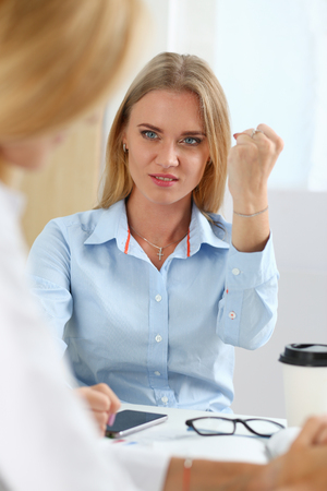 Photo for Angry yelling boss pointing her arm to exit dismissing a sad worker - Royalty Free Image