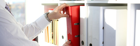 Photo pour Male arms pick red file folder from office book shelf - image libre de droit