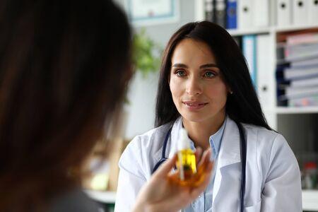 Photo pour Pretty cheerful female GP giving medical marijuana oil to patient portrait - image libre de droit