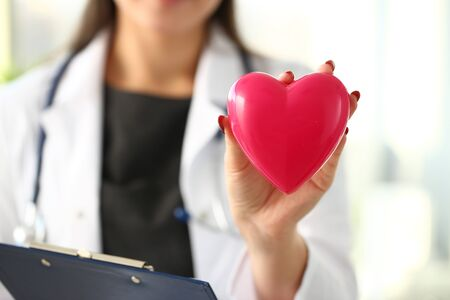 Foto de Beautiful smiling blond female doctor hold in arms red toy heart closeup. Cardio therapeutist student education CPR 911 life save physician make cardiac physical pulse rate measure arrhythmia - Imagen libre de derechos