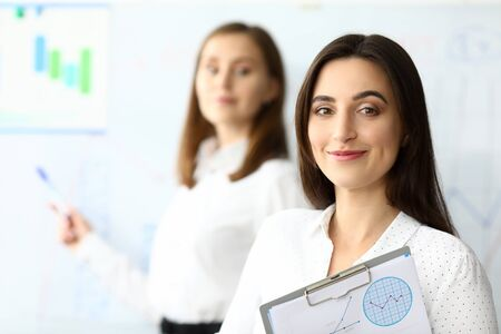 Foto de Portrait of smiling businesswoman sitting at comfortable workplace and looking at camera with smile. Pretty businesspeople discussing charts and graphs. Accounting office concept - Imagen libre de derechos