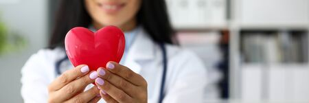 Foto de Female cardiolog holding in arms red toy heart closeup. Infarction protection and sickness prophylaxis long and healthy life concept - Imagen libre de derechos