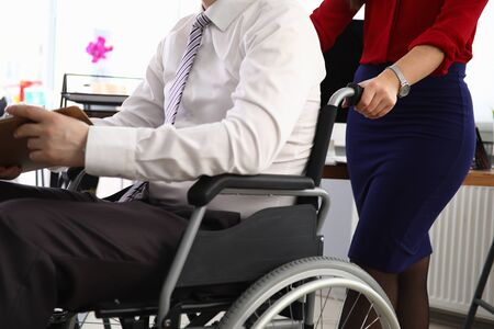 Photo pour Woman carries man in suit on wheelchair workplace. Person moves on wheelchair. Interview invitation. Wheelchair access to office. Person with disabilities returned to active work workplace - image libre de droit