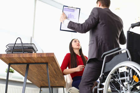 Photo pour A man in a suit got off the wheelchair with a report in his hands. The woman is surprised by the recovery of the boss - image libre de droit