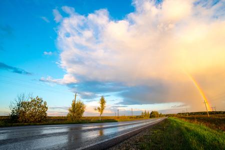 Foto de Landscape with country road and rainbow. - Imagen libre de derechos