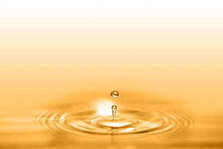 Photo for Closeup on drop of cosmetic golden oil liquid creating a circular wave. - Royalty Free Image