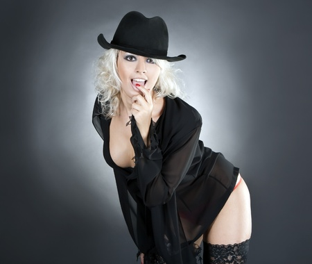 blonde fashion woman portrait wearing black hat over dark