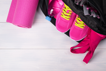 Photo pour Pink set in a sports bag on a gray board background - image libre de droit