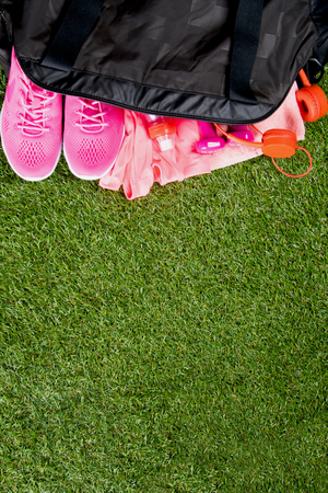 pink clothes and accessories for fitness, a bottle of water, in a black sports bag, on the background of grass, with a place for writing