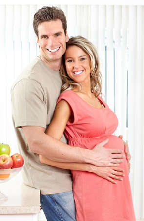 Smiling beautiful pregnant woman and man  at kitchen
