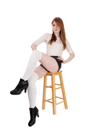 Photo for A lovely brunette woman sitting on chair in shorts and long white socks and high heels with legs crossed, isolated for white background  - Royalty Free Image