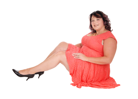 Photo for A beautiful big woman sitting in a red dress in the floor, smiling into the camera, isolated for white background  - Royalty Free Image