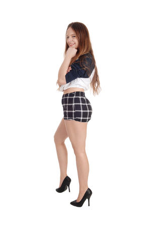 Photo for A full length image of a young slim woman standing in checkered shorts and heels, isolated for white background  - Royalty Free Image