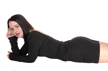 Foto de A beautiful young lying in a black dress and black hair on her stomach on the floor with her nice figure, isolated for white background - Imagen libre de derechos