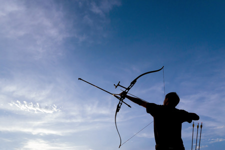 Photo for A silhouette of an archer drawing his bow and aiming upwards with deep blue sky and white clouds as background - Royalty Free Image