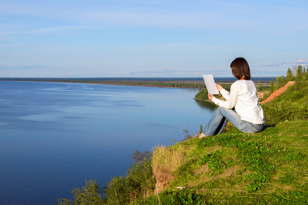 Young woman sitting on the shore of the lake with blank sheet of paper