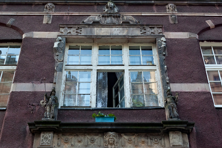 Photo for Open aged shabby window with bas-reliefs on one of the historic buildings in the Main Town of Gdansk. Poland. - Royalty Free Image