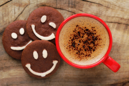 Foto de Good morning or Have a nice day message concept - bright red cup of frothy coffee with smiling chocolate cookies - Imagen libre de derechos