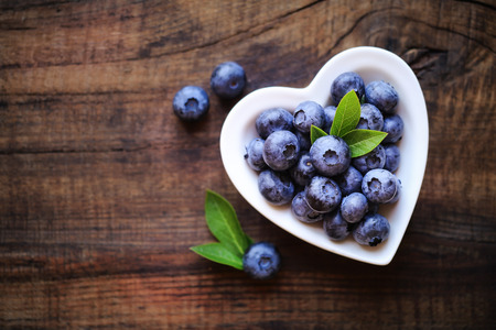 Photo pour Fresh ripe garden blueberries in a white heart shape bowl on dark rustic wooden table. with copy space for your text - image libre de droit
