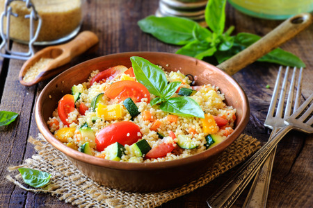 Photo pour Delicious homemade vegetarian couscous with tomatoes, carrots, zucchini, yellow bell pepper and fresh basil on a dark rustic wooden kitchen table - image libre de droit