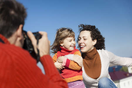 father make photos of his wife and daughter,selective focus