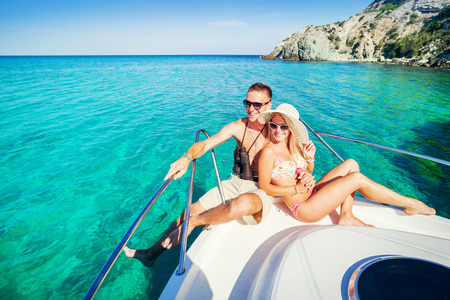 Foto de Romantic happy couple in love relaxing on a yacht at sea. Man and woman lying and hugging on a private boat cruising on the islands. Luxury holidays on the water. - Imagen libre de derechos