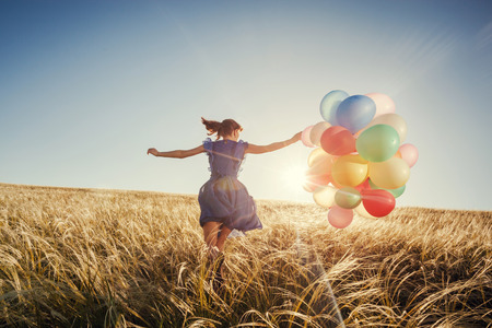 Foto de Girl running on the field with balloons at sunset. Happy woman on nature. - Imagen libre de derechos