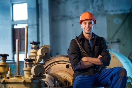 Foto de Portrait of a worker in the helmet near the turbine. Work the factory - Imagen libre de derechos