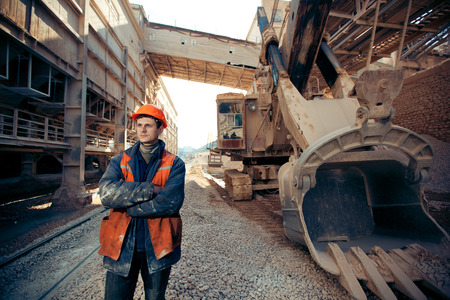 Foto de portrait of the working man in a helmet and work clothes near the excavator on a career - Imagen libre de derechos
