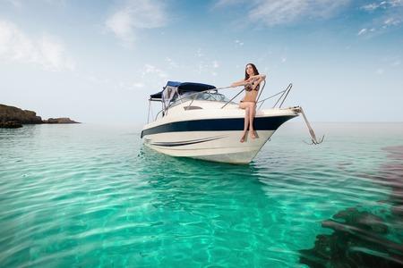 Foto de young beautiful girl sitting on a yacht at sea. Relaxing on the water - Imagen libre de derechos